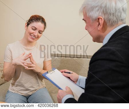 Mature Gray-haired Male Psychotherapist With Clipboard In Session With Female Patient. Smiling Cauca