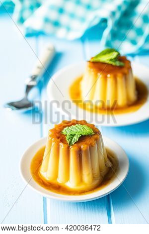 Sweet vanilla pudding. Sweet dessert with caramel topping on blue table.