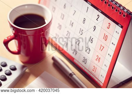 Calendar on desk in office with calculator and pen, business deadline, appointment and meeting concept