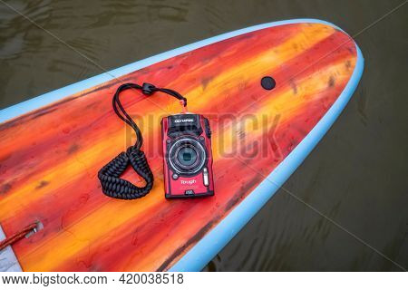 Fort Collins, CO, USA - May 9, 2021: Compact, waterproof Olympus Stylus Tough TG-5 camera on a rear deck of a stand up paddleboard by Mistral.