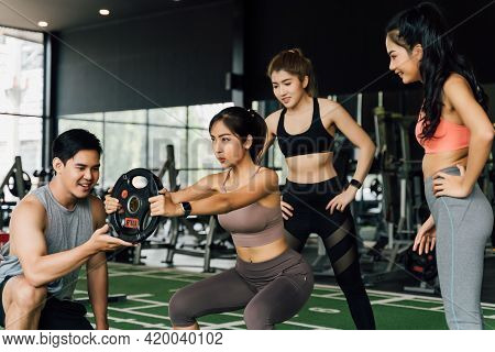 Group Of People Cheering On Their Asian Female Friend Doing Squats With A Weight Plate In Fitness Gy