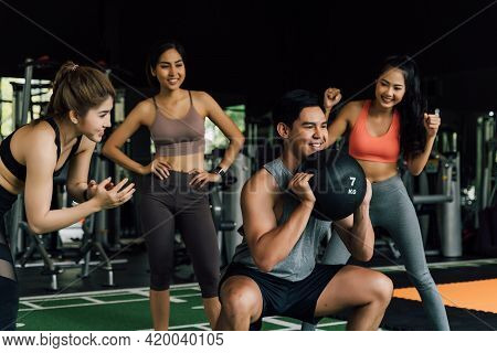 Group Of People Cheering On Their Asian Chinese Male Friend Doing Squats With A Medicine Ball In Fit