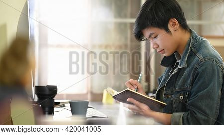 Smart Man Writing On Notebook/taking Note While Sitting And Relaxing At The Black Leather Sofa Over