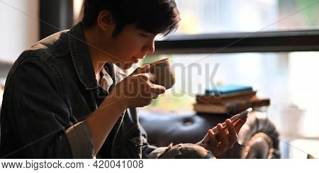 Cropped Image Of Smart Man Drinking A Hot Coffee And Holding/using A White Blank Screen Smartphone W