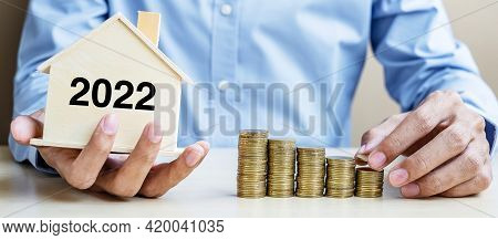 Business Man Hand Putting Golden Coin On Growing Money Stairs With 2022 Wood Home. Happy New Year Bu