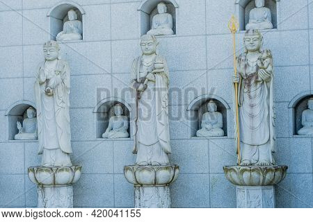 Three Standing Buddha Statues In Front Wall Of Seated Buddhas In Small Alcoves.