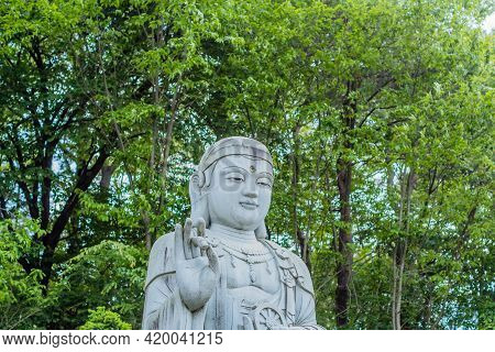 Closeup Of Large Stone Carved Seated Buddha In Front Of Lush Green Trees.