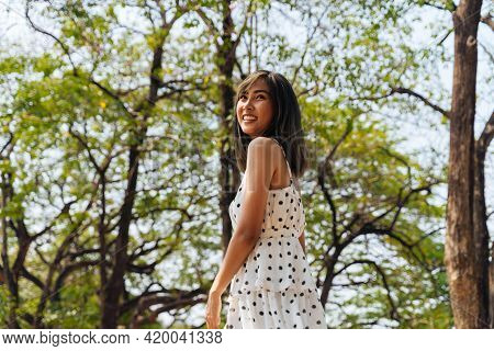 Happy And Carefree Young 20s Woman Dancing In The Outdoor Forest With Green Trees. Portrait Of Beaut