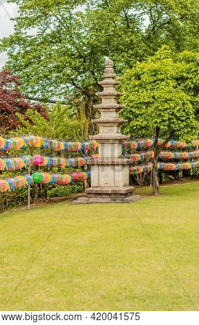 Stone Carved Pagoda In Lawn Beside Rows Of Paper Lanterns.