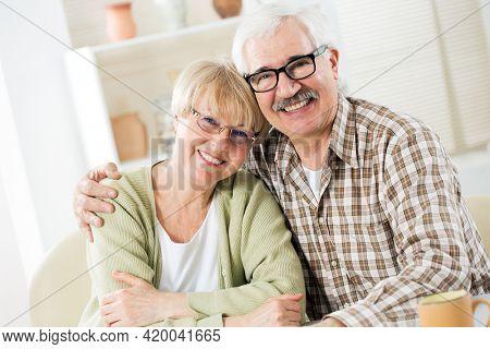 Happy elderly couple hugging at home and smiling at camera