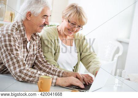 Happy elderly couple talking using laptop having breakfast together