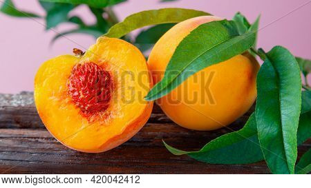 Peach In Halves With Bone. Peaches With Leaves On Wooden Board. Ripe Juicy Peaches. Harvest Of Peach