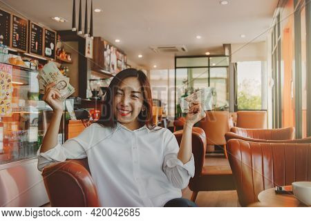Portrait Beautiful Woman Sitting In A Coffee Shop, Showing A Five Thousand Baht Thai Banknote, Along