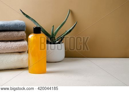 Shampoo, Gel, Orange Liquid Soap Made From Natural Ingredients In A Transparent Bottle Stands On A B