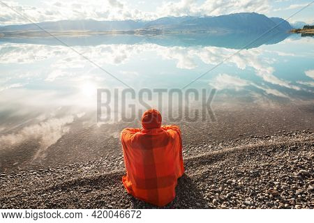 A man is resting at ease by the calm lake. Relaxation vacation