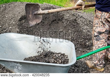 Unidentified Man Pours Gravel Into A Wheelbarrow. As Part Of A Construction Project, A Man Is Transp