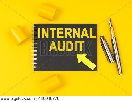 Business And Finance Concept. On A Yellow Background Lies A Pen, A Black Notebook With The Inscripti