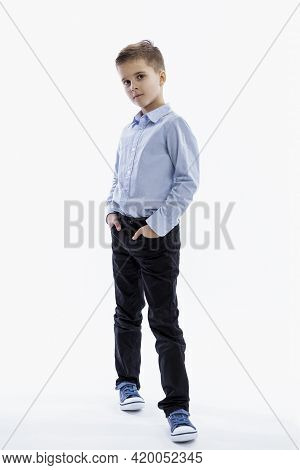 A Serious Boy Of 7 Years Old Is Standing. Full Height. White Background. White Background. Vertical.