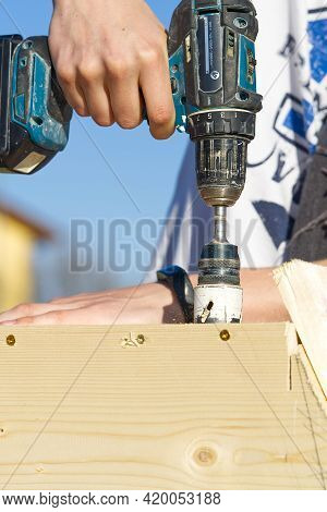 Hole Saw For Wood Drills A Hole In The Birdhouse. A Young Master Makes A Birdhouse And Drills A Hole