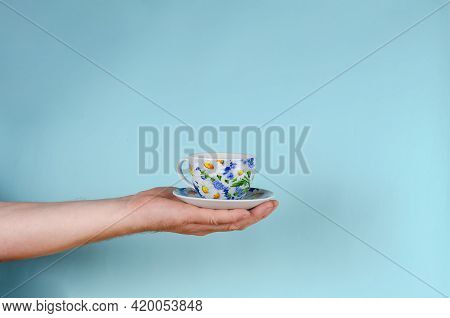 Hand And Cup On Blue Background. Man Holding White Cup With Painted Flowers. Ceramic Mug Cup And Sau