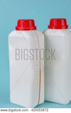 Two White Containers With Lid For Liquids On Blue Background. Rectangular Plastic Generic Bottle Wit