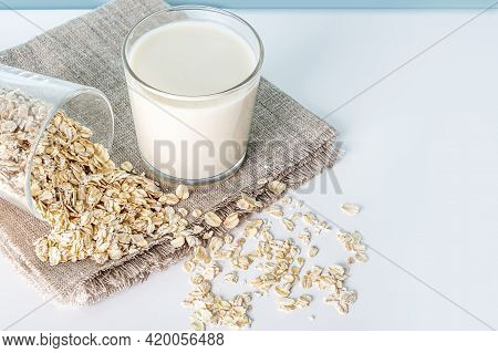 Glass Of Oat Vegetable Milk And Scattered Oat Flakes On Table. Concept Of Making Plant Based Organic