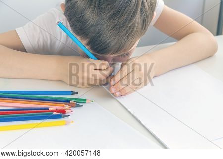 Focused Preschooler Little Boy 5-6 Years Painstakingly Draws Drawing By Pencil. Doing Homework, Draw