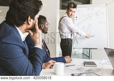 Company Leader Standing Near The Flipchart. A Team Of Young Businessmen Working And Communicating To