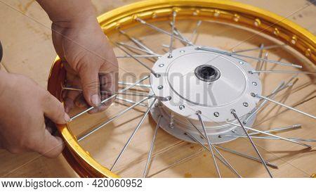 Technician Man Working Motorcycle Wheel Has Spokes Weave Up On Mechanic New Steel Wheel, Motorcycle
