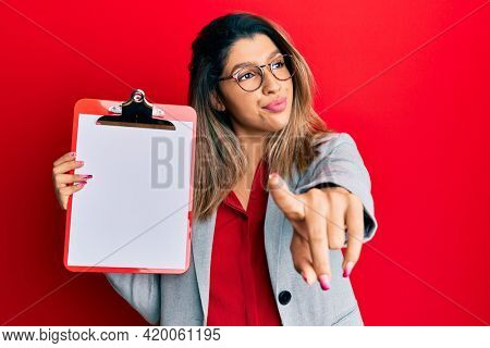 Beautiful brunette woman holding clipboard with blank space smiling looking to the side and staring away thinking.