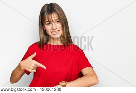 Teenager caucasian girl wearing casual red t shirt in hurry pointing to watch time, impatience, upset and angry for deadline delay