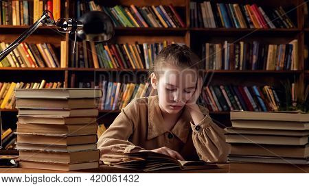 Young Lady In Brown Jacket Reads Training Materials In Textbook Preparing For Lessons Sitting Agains