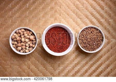 Chili Powder, Coriander Seed And Cardamom In A Bowl On Woven Bamboo Background, Asian Food Ingredien