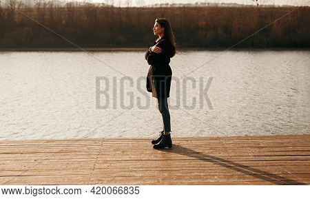 Side View Of Peaceful Female In Coat Standing On Wooden Quay And Admiring View Of Pond At Sundown In