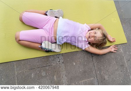 Cute Happy Little Girl In Sportswear Looking At Camera And Smiling While Laying On Yoga Mat And Exer