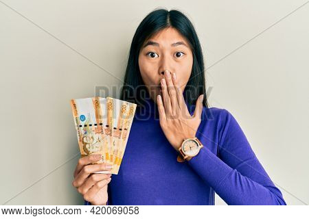 Young chinese woman holding 500 philippine peso banknotes covering mouth with hand, shocked and afraid for mistake. surprised expression