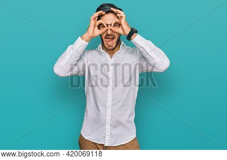 Young hispanic man wearing business shirt and glasses doing ok gesture like binoculars sticking tongue out, eyes looking through fingers. crazy expression.