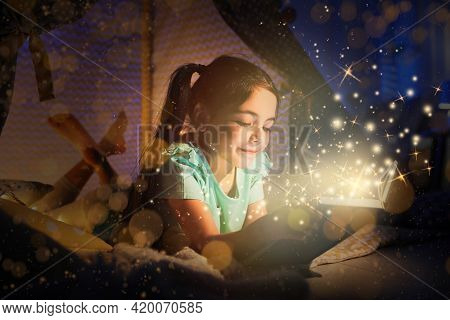 Little Girl Reading Fairy Tale In Play Tent At Home