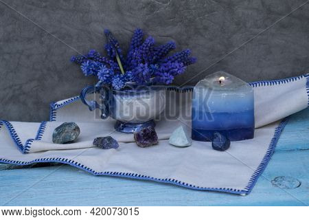 There Is A Bouquet Of Muscari In The Cup, A Blue Candle Is Burning Next To It. In Front Are Natural