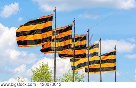 St. George Flags Of Victory Waving In The Wind Against The Background Of The Sky. Black Orange Strip