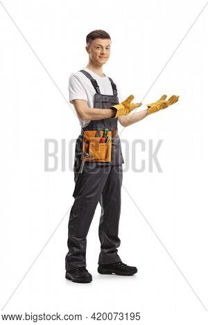 Full length portrait of a young repairman with a tool belt gesturing welcome isolated on white background