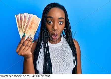 Young african american woman holding 500 norwegian krone banknotes scared and amazed with open mouth for surprise, disbelief face