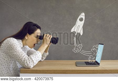 Surprised Woman With Binoculars Looking At Rocket Flying Out Of Laptop Computer Screen