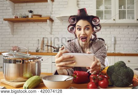 Crazy Woman In Bathrobe And Hair Curlers Makes Funny Selfie With Outstretched Tongue On Phone.
