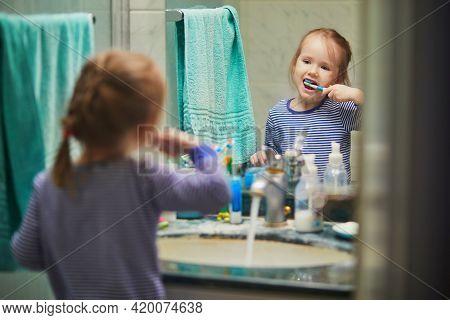 Happy Toddler Girl In Pyjamas Brushing Her Teeth In Bathroom In The Morning Or Before Going To Sleep