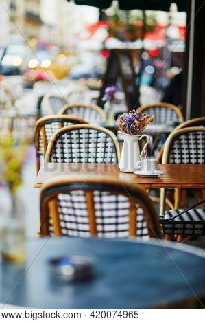 Table Of Traditional Parisian Outdoor Cafe. Cup Of Coffee And Pitcher With Dried Flowers In Empty Re