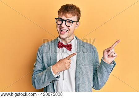 Young caucasian nerd man wearing glasses wearing hipster elegant look with bowtie smiling and looking at the camera pointing with two hands and fingers to the side.