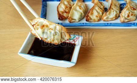 Fried Japanese Gyoza Dumplings On A Wooden Table.