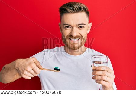 Young redhead man holding toothbrush with toothpaste and glass of water smiling with a happy and cool smile on face. showing teeth.