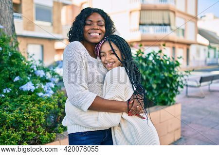Beautiful african american mother and daughter smiling happy and hugging. Standing with smile on face standing at the park